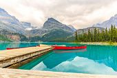 stock photo of dock a lake  - Red canoes docking at Idyllic Lake O - JPG