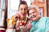 picture of granddaughter  - Senior woman and granddaughter having fun eating ice cream sundae in cafe - JPG