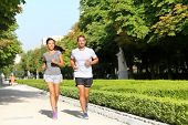 image of woman couple  - Running couple runners jogging in city park - JPG
