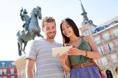 image of visitation  - Madrid tourists using tablet travel app guidebook ebook on Plaza Mayor by statue of King Philip III - JPG