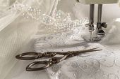 stock photo of scissors  - Antique scissors against wedding dress material and sewing machine - JPG