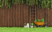 image of wheelbarrow  - Garden with an old wooden fence and tools for gardening - JPG