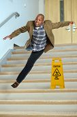 image of slip hazard  - African American businessman falling on stairs with yellow warning sign on steps - JPG