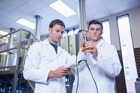 foto of beaker  - Two men in lab coat testing beer in the beaker in the factory - JPG
