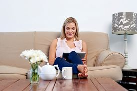 stock photo of couch  - Woman at home relaxing on sofa couch reading email on the tablet computer wifi connection - JPG