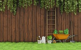 stock photo of wooden fence  - Garden with an old wooden fence and tools for gardening - JPG