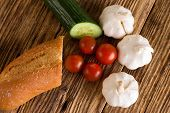 picture of baguette  - Horizontal photo of variable vegetable and baguette as red tomatoes green cucumber and white garlics - JPG