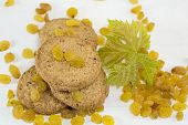 foto of baked raisin cookies  - Integral cookies and yellow raisins with a large green flower on white - JPG