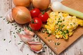 foto of scrambled eggs  - Horizontal photo of big portion of scrambled eggs with chopped chive on board with big salt seeds around and various vegetable as onions tomatoes and garlic - JPG