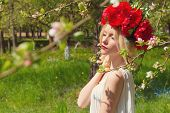 stock photo of woman red blouse  - beautiful young gentle elegant young blond woman with red peony in a wreath of white blouse walking in the lush apple orchard - JPG
