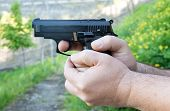 image of pistols  - Detail of mans hands holding automatic pistol - JPG
