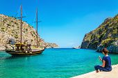 stock photo of greek-island  - Young lady sitting and eating icecream on bank of cosy port on Greek Island with old wooden yacht in background in silent bay - JPG