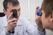 stock photo of infirmary  - ophthalmologist examines the eyes of a teenager through a magnifying glass - JPG