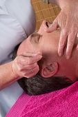 foto of pointed ears  - Acupuncturist prepares to tap needle on man - JPG