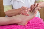 Acupuncturist Prepares To Tap Needle On The Foot Of A Man poster