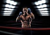 stock photo of boxing ring  - A strong man in the ring in blue boxing bandages preparing for battle - JPG