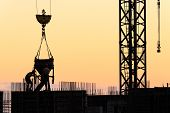 pic of concrete pouring  - Builders poured concrete in a new building at sunset - JPG