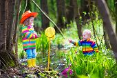 picture of wild adventure  - Children playing outdoors. Two preschooler kids catching frog with colorful net. Little boy and girl fishing in a forest river in summer. Adventure kindergarten day trip into wild nature young explorer hiking and watching animals.