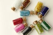 pic of beads  - Tiny glass bottles filled with beads of different colors - JPG
