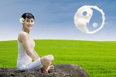 stock photo of ying-yang  - Happy girl and ying yang cloud outdoor on green field - JPG
