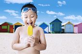 stock photo of beach hut  - Portrait of cheerful male kid standing on the shore while licking a yummy ice cream with the background of the beach huts - JPG