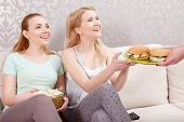 stock photo of pajamas  - Small lunch. Two young beautiful girls wearing pajamas sitting on a couch holding a bow with popcorn and taking a plate with sandwiches