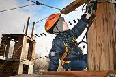 image of suspension  - little boy sits on suspension bridge and adjusts equipment - JPG