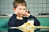 foto of milk  - Angry little boy sitting at the dinner table - JPG