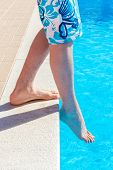 pic of toe  - Teenage boys legs wearing swimming trunks with toes of foot feeling water temperature in blue swimming pool - JPG