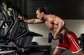 pic of mature men  - Muscular Mature Man Doing Heavy Weight Exercise For Back With Dumbbell In Modern Fitness Center - JPG