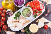 stock photo of nachos  - Guacamole in porcelain Bowl with mexican Tortilla Chips nachos and Ingredients - JPG