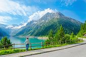 image of beside  - A young woman stands beside an azure mountain lake on the background of the high peaks of the Alps - JPG