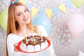 picture of cone  - Portrait of a young beautiful blond girl wearing cone cap holding a red plate with birthday cake with candles in the light decorated room - JPG