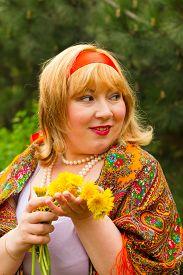 foto of cheeky  - Cheeky Russian cheerful young woman in a wreath of fresh dandelion flirt flirty look - JPG