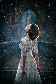 Lovely young lady wearing elegant white dress enjoying the beams of celestial light and snowflakes poster