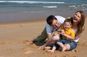 image of family fun  - Happy family of three having fun at the beach - JPG