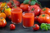 Fresh tomato juice in a transparent glass and ripe tomatoes on the background. Tomato Fresh. Tomato  poster
