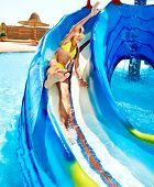 stock photo of amusement park rides  - Child on water slide at aquapark - JPG