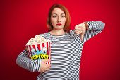 Young beautiful redhead woman eating popcorn over red isolated background with angry face, negative  poster