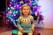 Adorable Toddler Girl Sitting Near Christmas Tree. Little Child Playing And Decorating Xmas Tree Wit poster
