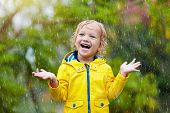 Kids Play In Autumn Rain. Child On Rainy Day. poster