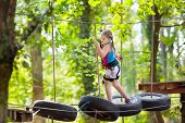 Child In Adventure Park. Kids Climbing Rope Trail. poster