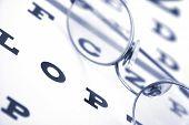 stock photo of snellen chart  - eye glasses over eye chart  - JPG