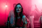 Beautiful Girl Holding Beer In Nightclub And Dancing During Rave poster