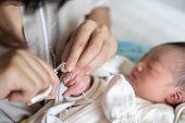 Asian Baby Getting Fingernails Cut. poster