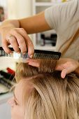 Female Hairdresser Making Hairstyle To Blonde Girl In Beauty Salon. Closeup View. Hairdressing Servi poster
