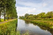 Long And Straight Canal In A Rural Landscape In The The Dutch Summer Season. Along The Canal Is A Ro poster