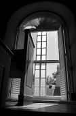 picture of pews  - This black and white image shows the side of a church pew in front of a beautiful historical window - JPG