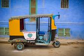 stock photo of rickshaw  - Traditional motorized rickshaw againsta a blue wall in Jodhpur Rajasthan India - JPG