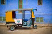 stock photo of rickshaw  - Traditional motorized rickshaw againsta a blue wall in Jodhpur Rajasthan India - JPG